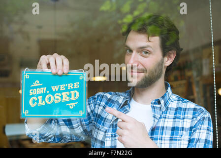 Worker hanging shop closed sign - Stock Photo