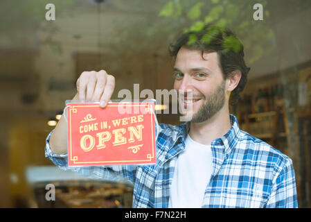 Businessman opening shop for business - Stock Photo
