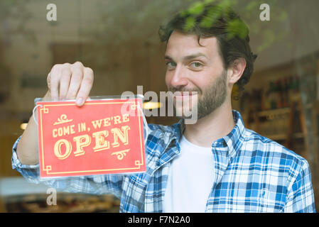 Business owner opening shop for the day - Stock Photo