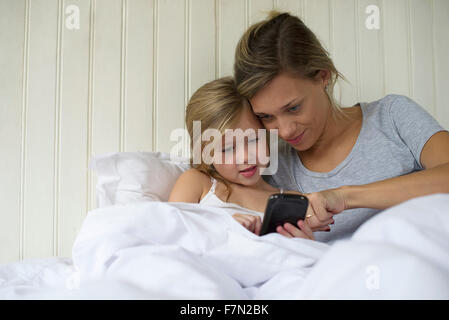 Mother and daughter using smartphone together - Stock Photo