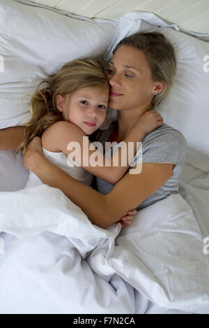 Mother and daughter in bed embracing - Stock Photo