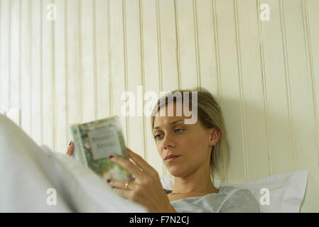 Woman reading in bed - Stock Photo