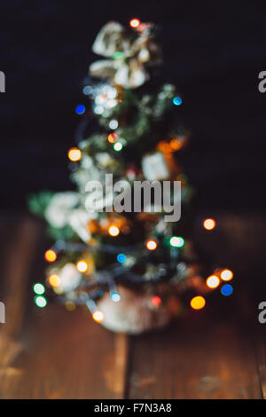 Small Christmas tree with garland on the wooden background - Stock Photo