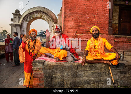 Three Shaiva sadhus (holy men) in traditional clothing in ancient Pashupatinath Temple - Stock Photo