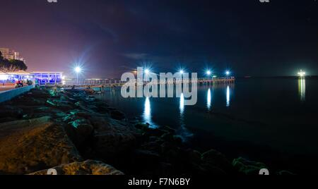 The Limassol pier in Enaerios Area in Cyprus. A night view of the city lights and the moon rising from the sea reflected - Stock Photo