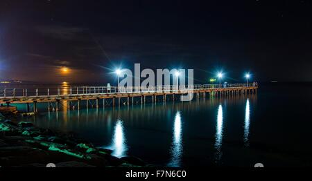 The Limassol pier in Enaerios Area in Cyprus. A night view of the city lights aligning to the moon as it rises from - Stock Photo