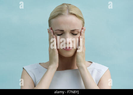 Woman holding face in hands, eyes closed - Stock Photo