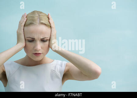 Woman holding hands over ears, looking down with furrowed brow - Stock Photo
