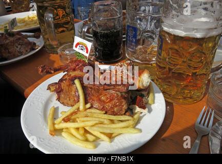 Oktoberfest beer steins and festival food, half chicken & fries, Munich, Germany - Stock Photo