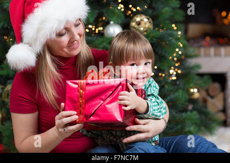 Happy woman gives wrapped christmas presents gifts to child baby toddler sitting near Christmas tree - Stock Photo