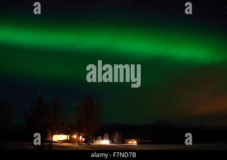 green strong aurora borealis over field and homes in the arctic circle winter landscape - Stock Photo