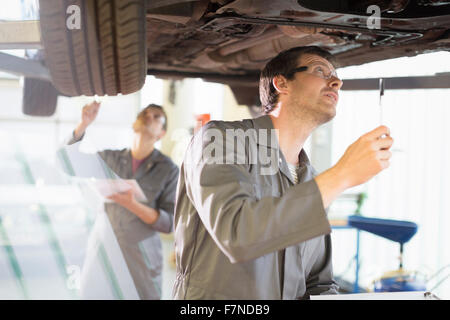 Mechanic working under car in auto repair shop - Stock Photo