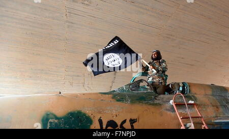Islamic State fighter (ISIS; ISIL) waving a flag while standing on captured government fighter jet in Raqqa, Syria - Stock Photo