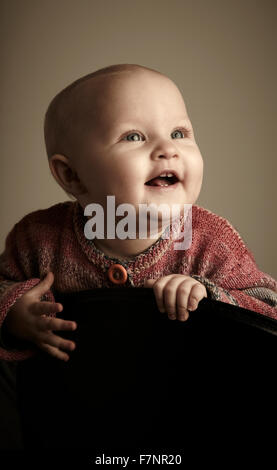 baby girl (8 month) looking cheerful and with expectation towards the light - Stock Photo
