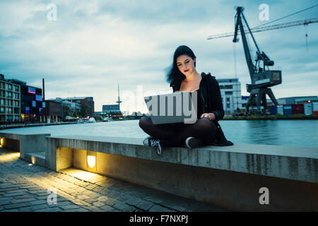 Germany, Muenster, young woman with laptop sitting in front of city harbour - Stock Photo