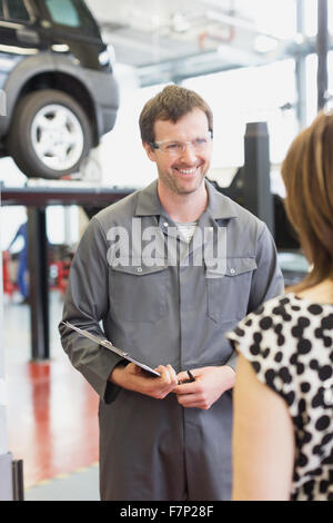 Mechanic with clipboard talking to customer in auto repair shop - Stock Photo