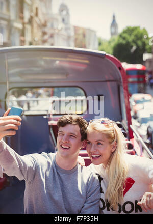 Couple taking selfie on double-decker bus in London - Stock Photo