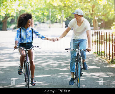 Couple holding hands riding bicycles in urban park - Stock Photo