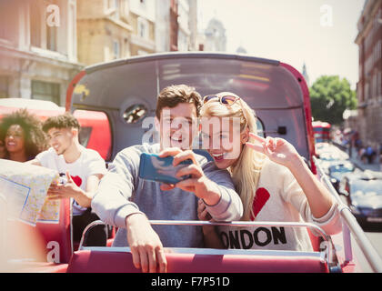 Couple taking selfie on double-decker bus, London, United Kingdom - Stock Photo
