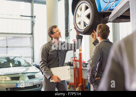 Mechanics examining and discussing tire in auto repair shop - Stock Photo