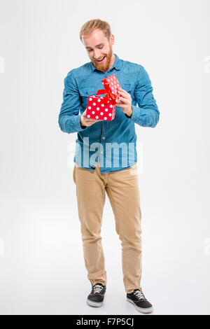 Full length portrait of cheerful joyful young blond bearded man opening gift isolated over white background - Stock Photo