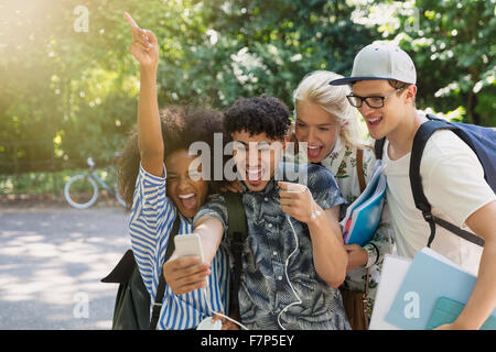 Enthusiastic college students taking selfie in park - Stock Photo