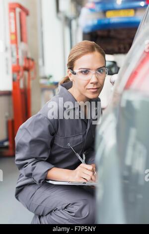 Focused female mechanic taking notes in auto repair shop