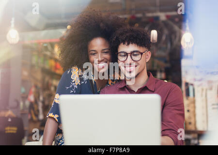 Couple using laptop at cafe window - Stock Photo