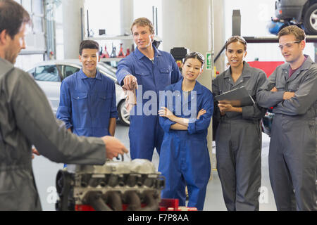 Mechanic and students discussing car engine in auto repair shop - Stock Photo