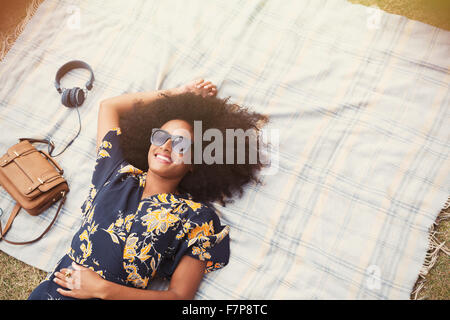 Overhead view smiling woman with afro laying on blanket outdoors - Stock Photo