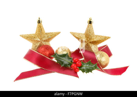 Christmas decoration of two glitter stars, red ribbon and baubles with holly isolated against white - Stock Photo