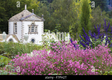 The Pin Mill seen from behind a cloud of pink Diascia flowers at Bodnant Garden, Conwy, Wales, in October. - Stock Photo