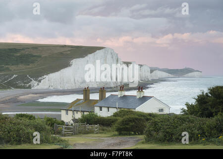 Stormy skies over the coastgard cottages at Cuckmere Valley, East Sussex, with the Seven Sisters seen beyond. - Stock Photo