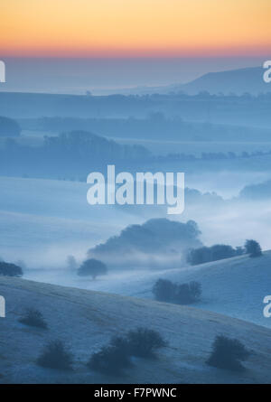 A misty view across the Sussex Downs at dawn, from Ditchling Beacon, East Sussex. - Stock Photo