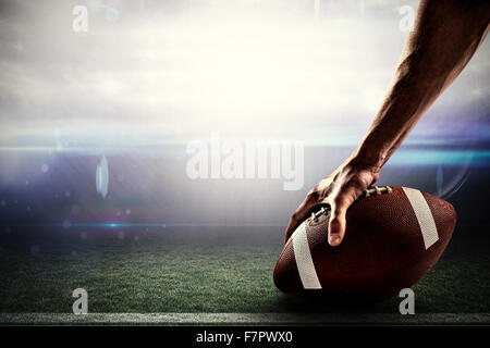 Composite image of cropped image of sports player holding ball - Stock Photo
