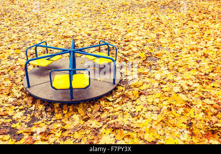 Lonely abandoned carousel in autumn park full of yellow maple leaves - Stock Photo