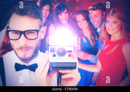 Composite image of geeky hipster holding a retro camera - Stock Photo