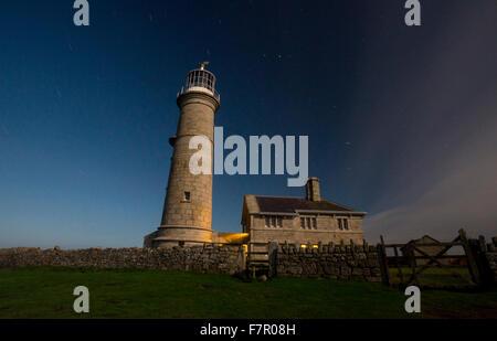 Lundy Old Light lighthouse against a deep blue night sky - Stock Photo