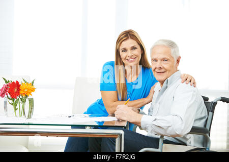 Woman and senior man filling out forms together at home - Stock Photo
