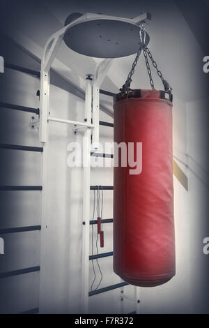 Red leather punching bag on a chain in gym - Stock Photo