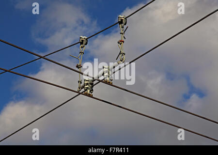 Overhead electric conductor wire with 'hangers' supporting the two main conductor wires and shows the fitting that - Stock Photo