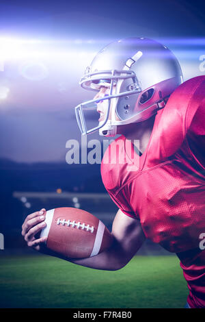 Composite image of side view of aggressive sportsman playing american football - Stock Photo
