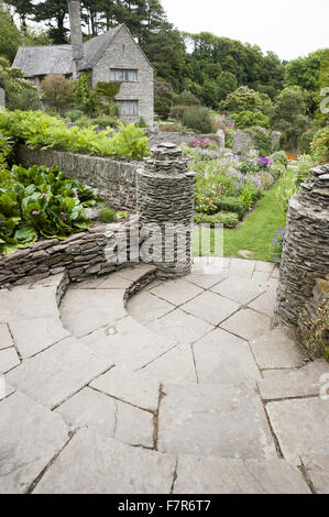Curved steps leading down to the Rill Garden, planted with pastel coloured flowers, at Coleton Fishacre, Devon. - Stock Photo