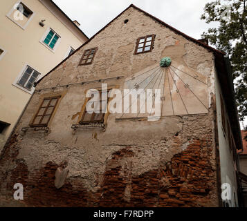 Very old house that has a sun clock on a side wall. Image taken in Zagreb, Croatia. - Stock Photo