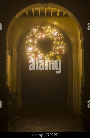 Giant Christmas wreath, glowing with fairy lights and hanging from an archway at Polesden Lacey, Surrey. - Stock Photo