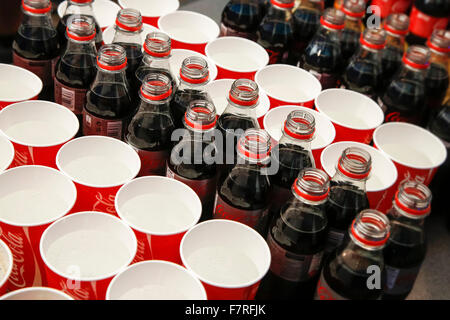 Open plastic Coca Cola bottles and throwaway cups with sparkling water at event - Stock Photo