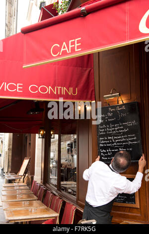 A waiter hanging the day's menu out a cafe in the Marais district of Paris, France - Stock Photo