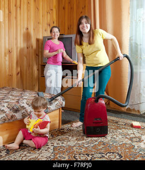 Family is cleans living room with vacuum cleaner - Stock Photo
