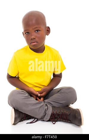 sad African American boy sitting on white background - Stock Photo