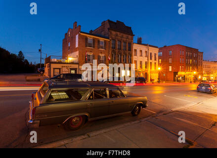 Walton Street with a Rambler Ambassador in the foreground in downtown Port Hope at dusk. Ontario, Canada. - Stock Photo
